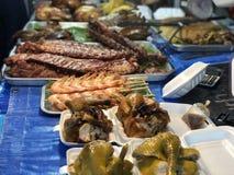 Ταϊλανδική αγορά νύχτας με τα εθνικά τρόφιμα: τηγανισμένα ψάρια, σούσια, γλυκά ρυζιού, οβελίδια, σούσια, θαλασσινά στοκ εικόνα
