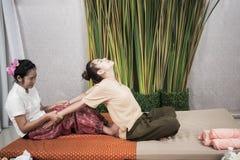Ταϊλανδική μασέρ που κάνει το μασάζ για τη γυναίκα στο σαλόνι SPA Ασιατική όμορφη γυναίκα που παίρνει το ταϊλανδικό βοτανικό μασά Στοκ Εικόνα