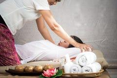 Ταϊλανδική μασέρ που κάνει το μασάζ για τη γυναίκα στο σαλόνι SPA Ασιατική όμορφη γυναίκα που παίρνει το ταϊλανδικό βοτανικό μασά Στοκ εικόνα με δικαίωμα ελεύθερης χρήσης