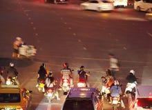 Ταϊλανδικοί λαοί που οδηγούν τις μικρές μοτοσικλέτες που περιμένουν κόκκινο σε άφθονο στοκ φωτογραφία