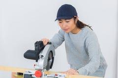Ταϊλανδικός ξυλουργός κοριτσιών που χρησιμοποιεί το κυκλικό πριόνι Στοκ Εικόνα