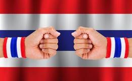 Ταϊλανδικό εθνικό ύφασμα χρώματος wristband στον καρπό τύπων ` s στο κυματίζοντας εθνικό υπόβαθρο σημαιών της Ταϊλάνδης Στοκ Εικόνα