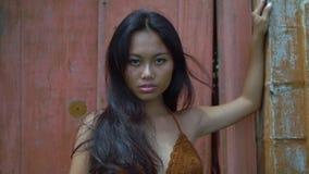 Ταϊλανδικό κορίτσι στην τοποθέτηση καφετιών κορυφών υπαίθρια, στάσεις ενάντια στην κόκκινη ξύλινη πόρτα, κινηματογράφηση σε πρώτο φιλμ μικρού μήκους