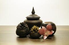 Ταϊλανδικό ξύλινο κύπελλο ύφους με το πεύκο κώνων στον ορείχαλκο με το λουλούδι ορχιδεών Στοκ εικόνες με δικαίωμα ελεύθερης χρήσης