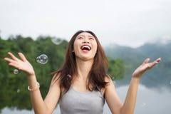 Ταϊλανδικό χαμόγελο κοριτσιών και ευχαριστημένος από τις αεροφυσαλίδες στοκ εικόνες