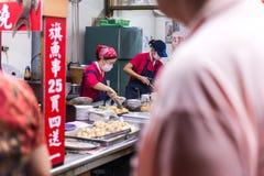 ΤΑΪΠΈΙ, ΤΑΪΒΑΝ - 10.2017 ΟΚΤΩΒΡΙΟΥ: Οι γυναίκες που μαγειρεύουν τα παραδοσιακά τρόφιμα μέσα στην αγορά Jiufen είναι μια γειτονιά  Στοκ Φωτογραφία