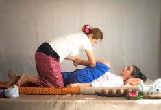 Ταϊλανδική μασέρ που κάνει το μασάζ για τη γυναίκα στο σαλόνι SPA Ασιατική όμορφη γυναίκα που παίρνει το ταϊλανδικό βοτανικό μασά Στοκ Εικόνες