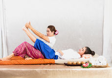 Ταϊλανδική μασέρ που κάνει το μασάζ για τη γυναίκα στο σαλόνι SPA Ασιατική όμορφη γυναίκα που παίρνει το ταϊλανδικό βοτανικό μασά Στοκ φωτογραφία με δικαίωμα ελεύθερης χρήσης