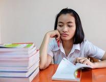 Ταϊλανδικός νέος ενήλικος σπουδαστής γυναικών στην ομοιόμορφη ανάγνωση ένα βιβλίο Στοκ Εικόνα