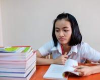 Ταϊλανδικός νέος ενήλικος σπουδαστής γυναικών στην ομοιόμορφη ανάγνωση ένα βιβλίο Στοκ φωτογραφία με δικαίωμα ελεύθερης χρήσης