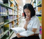 Ταϊλανδικός νέος σπουδαστής γυναικών που διαβάζει ένα βιβλίο Στοκ εικόνα με δικαίωμα ελεύθερης χρήσης