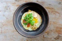 Ταϊλανδικός ξάδελφος, πιάτο αυγών στο μαύρο δοχείο αργίλου στον ξύλινο πίνακα Στοκ Φωτογραφία