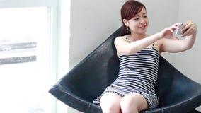 Ταϊλανδικό ενήλικο όμορφο κορίτσι επιχειρηματιών που χρησιμοποιεί το έξυπνο τηλέφωνό της Selfie φιλμ μικρού μήκους