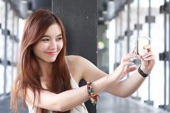Ταϊλανδικό ενήλικο όμορφο κορίτσι που χρησιμοποιεί το έξυπνο τηλέφωνό της Selfie Στοκ εικόνα με δικαίωμα ελεύθερης χρήσης