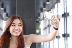Ταϊλανδικό ενήλικο όμορφο κορίτσι που χρησιμοποιεί το έξυπνο τηλέφωνό της Selfie Στοκ Φωτογραφίες