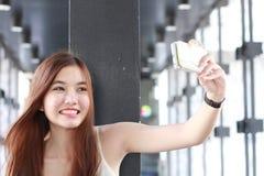Ταϊλανδικό ενήλικο όμορφο κορίτσι που χρησιμοποιεί το έξυπνο τηλέφωνό της Selfie Στοκ Εικόνες