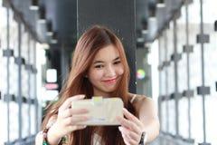 Ταϊλανδικό ενήλικο όμορφο κορίτσι που χρησιμοποιεί το έξυπνο τηλέφωνό της Selfie Στοκ Εικόνα