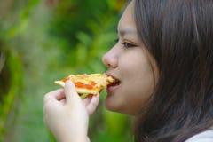 Ταϊλανδικό κορίτσι που τρώει την πίτσα στοκ φωτογραφία