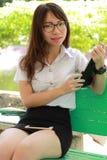 Ταϊλανδικό πανεπιστημιακό όμορφο κορίτσι σπουδαστών γυναικών που χρησιμοποιεί την ταμπλέτα της Στοκ φωτογραφία με δικαίωμα ελεύθερης χρήσης