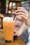 Ταϊλανδικό τσάι πάγου με το γάλα στο γυαλί με το χέρι στοκ φωτογραφία
