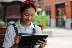 Ταϊλανδικό όμορφο κορίτσι εφήβων σπουδαστών που χρησιμοποιεί την ταμπλέτα της Στοκ Φωτογραφία