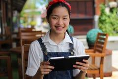 Ταϊλανδικό όμορφο κορίτσι εφήβων σπουδαστών που χρησιμοποιεί την ταμπλέτα της Στοκ Εικόνα