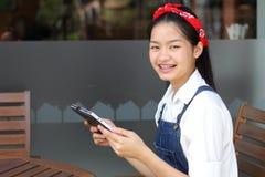 Ταϊλανδικό όμορφο κορίτσι εφήβων σπουδαστών που χρησιμοποιεί την ταμπλέτα της Στοκ φωτογραφίες με δικαίωμα ελεύθερης χρήσης