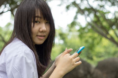 Ταϊλανδικό όμορφο κορίτσι εφήβων σπουδαστών που χρησιμοποιεί την έξυπνη τηλεφωνική συνεδρίασή της στο πάρκο Στοκ φωτογραφία με δικαίωμα ελεύθερης χρήσης