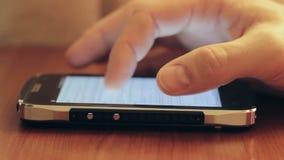 Τα άκρα δακτύλου προσώπων ` s αγγίζουν την οθόνη αφής του smartphone στον πίνακα απόθεμα βίντεο