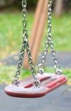 Ταλάντευση σε μια περιοχή παιχνιδιού παιδιών. Στοκ Φωτογραφία