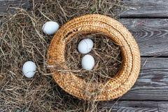 Τα άσπρα αυγά βάζουν στο κίτρινο καπέλο αχύρου ως φωλιά με τον ξηρό σανό μέσα στον ξύλινο ηλικίας πίνακα στοκ φωτογραφία με δικαίωμα ελεύθερης χρήσης