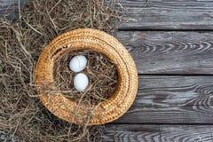 Τα άσπρα αυγά βάζουν στο κίτρινο καπέλο αχύρου ως φωλιά με τον ξηρό σανό μέσα στον ξύλινο ηλικίας πίνακα στοκ εικόνες
