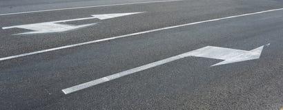 Τα άσπρα βέλη που δείχνουν το ρυθμιστικό οδικό σημάδι κατευθύνσεων προχωρούν στην κατεύθυνση που υποδεικνύεται από την κυκλοφορία στοκ φωτογραφία με δικαίωμα ελεύθερης χρήσης