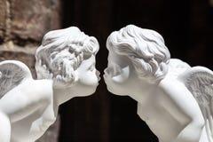 Τα άσπρα ειδώλια ασβεστοκονιάματος που φιλούν cupids, κλείνουν επάνω Στοκ Φωτογραφίες