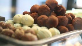 Τα άσπρα, καφετιά νόστιμα γλυκά με το ψέκασμα βρίσκονται στην αντίθετη κινηματογράφηση σε πρώτο πλάνο μεταλλικών πιάτων φιλμ μικρού μήκους