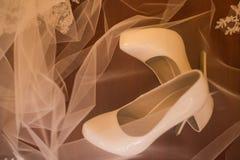 Τα άσπρα νυφικά παπούτσια καλύπτονται με ένα πέπλο Στοκ Εικόνες