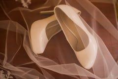 Τα άσπρα νυφικά παπούτσια παπουτσιών είναι καλυμμένα Γαμήλια εξαρτήματα Στοκ φωτογραφίες με δικαίωμα ελεύθερης χρήσης