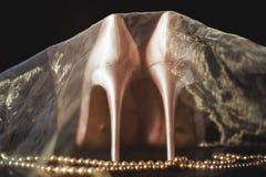 Τα άσπρα νυφικά παπούτσια παπουτσιών είναι καλυμμένα Στοκ Φωτογραφίες