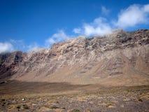 Τα άσπρα σύννεφα κατεβαίνουν από τις κλίσεις των ηφαιστειακών βουνών στην κοιλάδα σε ένα υπόβαθρο του βαθιού μπλε ουρανού Famara Στοκ φωτογραφία με δικαίωμα ελεύθερης χρήσης