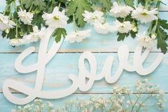 Τα άσπρα χρυσάνθεμα σε ένα ξύλινο υπόβαθρο και την επιγραφή αγαπούν το κέντρο, η τοπ άποψη στοκ εικόνες με δικαίωμα ελεύθερης χρήσης