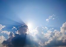Τα άσπροι χνουδωτοί σύννεφα και ο ήλιος απεικονίζουν, στο μπλε ουρανό στοκ εικόνες