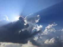 Τα άσπροι χνουδωτοί σύννεφα και ο ήλιος απεικονίζουν, στο μπλε ουρανό στοκ φωτογραφία με δικαίωμα ελεύθερης χρήσης