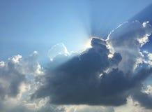 Τα άσπροι χνουδωτοί σύννεφα και ο ήλιος απεικονίζουν, στο μπλε ουρανό στοκ φωτογραφίες