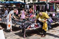 Τα άτομα επιλέγουν τα ενδύματα στην αγορά Aligre ψύλλων Γαλλία Παρίσι Στοκ Φωτογραφία