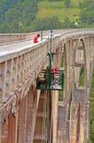 Τα άτομα εργάζονται σχηματισμένη αψίδα στη Durdevica γέφυρα της Tara πέρα από το πράσινο φαράγγι της Tara Στοκ Εικόνες