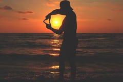 Τα άτομα κάνουν ένα επικεφαλής-διαμορφωμένο χέρι στο ηλιοβασίλεμα Στοκ εικόνα με δικαίωμα ελεύθερης χρήσης
