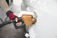 Τα άτομα κρατούν το ακροφύσιο καυσίμων για να προσθέσουν τα καύσιμα στο αυτοκίνητο στο πρατήριο καυσίμων Στοκ Φωτογραφία