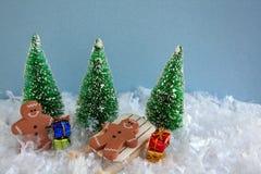 Τα άτομα μελοψωμάτων στο έλκηθρο με παρουσιάζουν και χριστουγεννιάτικα δέντρα Στοκ Εικόνες