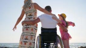 Τα άτομα με ειδικές ανάγκες αγκαλιάζουν τη σύζυγο και την κόρη, άκυρες με τη έγκυο γυναίκα και το παιδί στη θάλασσα υποβάθρου, ευ φιλμ μικρού μήκους