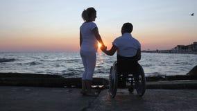 Τα άτομα με ειδικές ανάγκες και η γυναίκα ανυψώνουν επάνω παραδίδουν το βράδυ, άτομα με ειδικές ανάγκες με το έγκυο ηλιοβασίλεμα  φιλμ μικρού μήκους